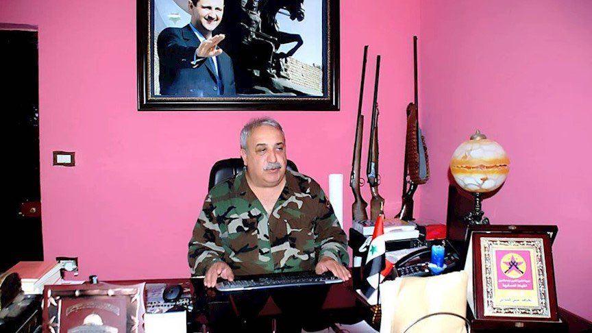 معراج أورال وخلفه صورة لرئيس النظام بشار الأسد